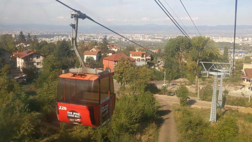קרון רכבל בעלייה לפסגת הר ויטושה עם נוף פנורמי אל עבר העיר סופיה בולגריה-min-min